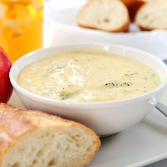 campbells cream of broccoli soup in a bowl next to bread, an apple, a drink