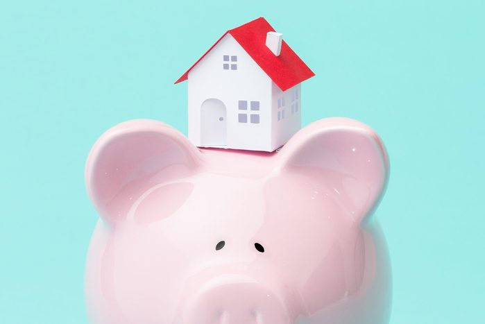 small house sitting atop a piggy bank against teal background