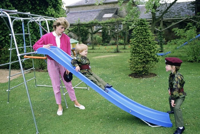 Princess Diana At Highgrove With Prince William And Prince Harry Dressed In Miniature Parachute Regiment Uniforms And Playing On Their Slide In The Garden