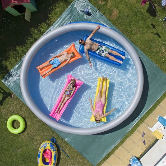 Family enjoying an inflatable pool in the summer time