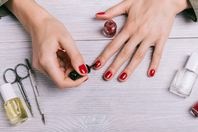 Close-up of a woman paints her nails with red lacquer