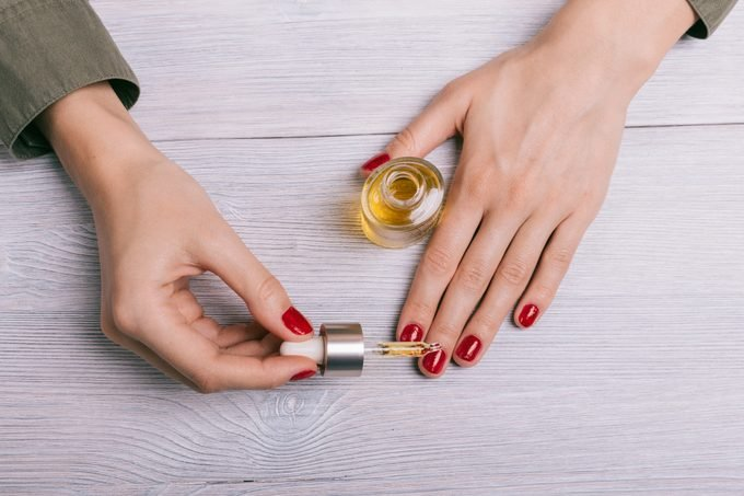 Female hand applied oil on the nails