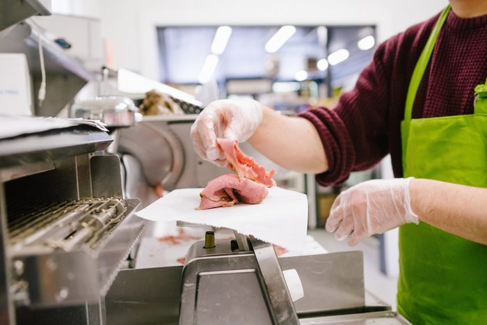 Employee in general store weighing sliced meat in kitchen