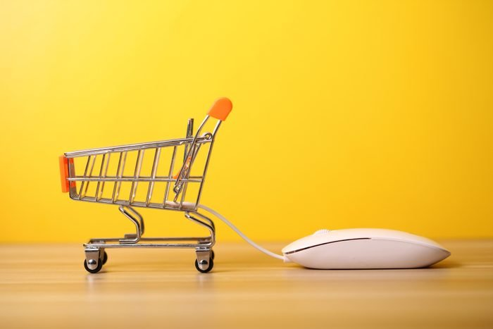 miniature shopping cart attached to the cord of a computer mouse on a wood desk, yellow background