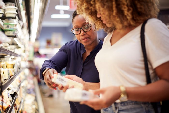 woman checking prices in grocery store