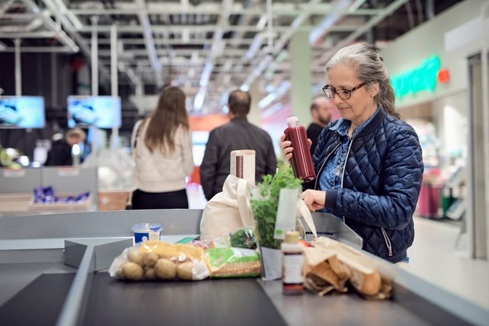 woman removing food from grocery check out line