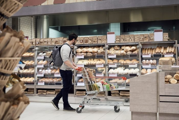 Side view of man walking with cart while looking at breads in supermarket