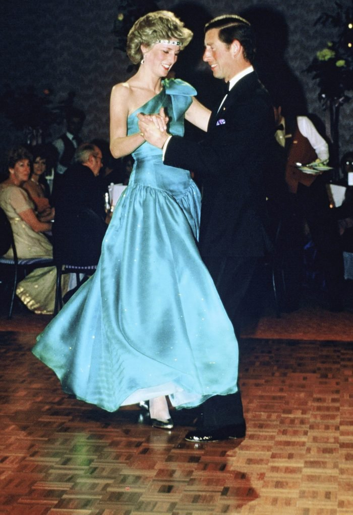 Prince Charles, Prince of Wales and Diana, Princess of Wales, wearing a green satin evening dress designed by David and Elizabeth Emanuel and an emerald necklace as a headband, dance together during a gala dinner dance at the Southern Cross Hotel on October 31, 1985 in Melbourne, Australia.