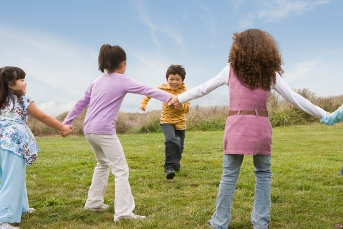 Multi Ethnic Children Playing Game In Field