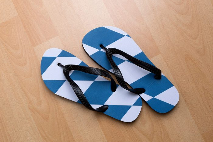 overhead view of a pair of flip flops on a wood floor