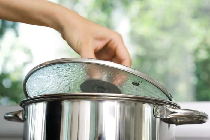 Person removing lid from cooking pot