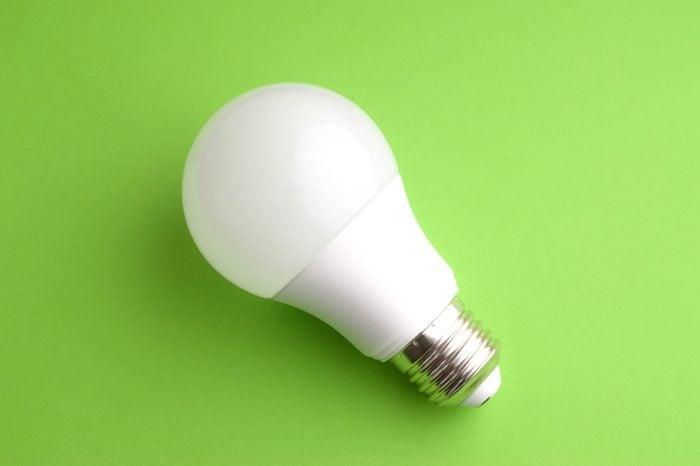 White led light bulb on green background