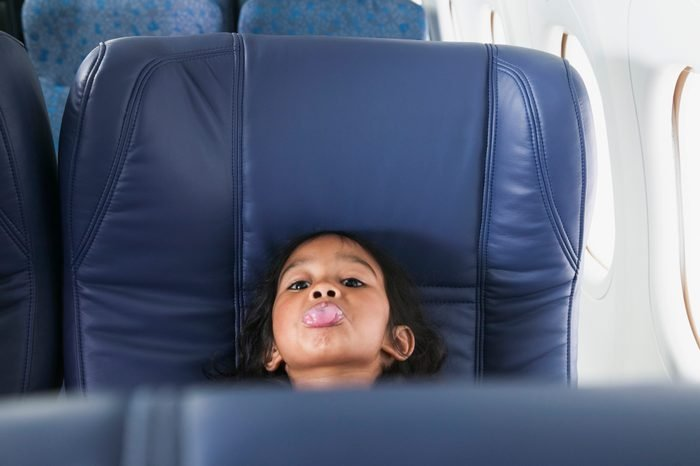Portrait of a young girl sitting in a seat showing her tongue in an airplane
