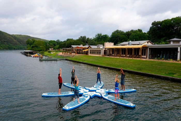paddleboard yoga class with exterior view of Lake Austin Spa Resort, Texas