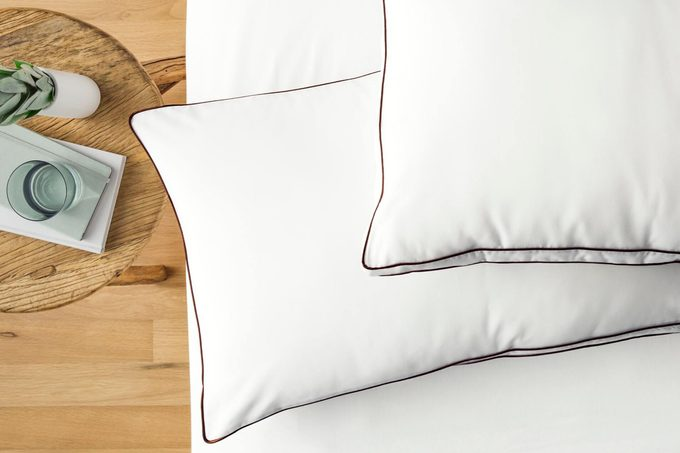 Saatva Latex Pillows on a bed next to a wood table