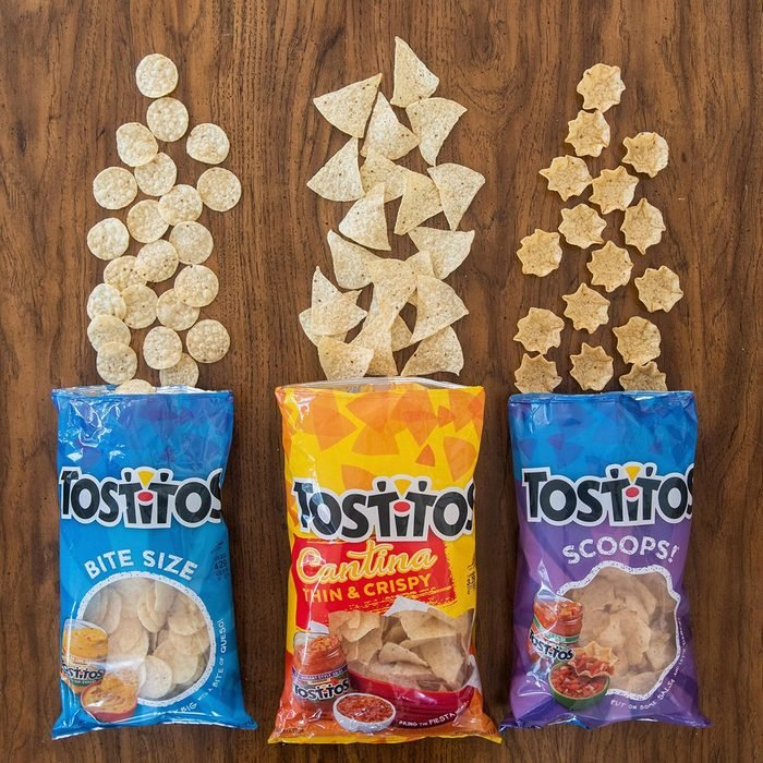 three variations of Tostitos Tortilla Chips laid out on wood background
