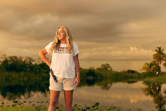 Anne Gorden-Vega with a knife in a snakeskin holster on her hip standing in front of the Everglades