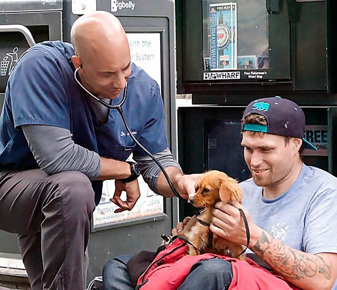 Dr. Stewart using a stethoscope on one of his homeless client's dog