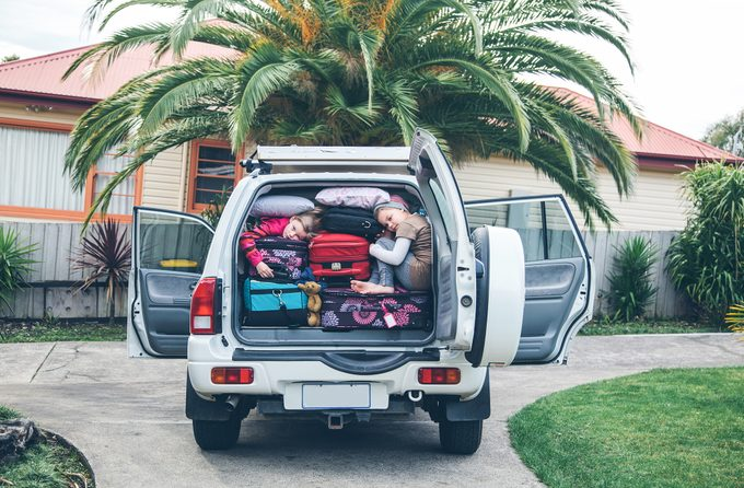Children squashed into the back of a heavilly loaded car with luggage
