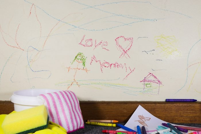 Child's crayon graffiti love mommy wall art drawing with crayons and cleaning material