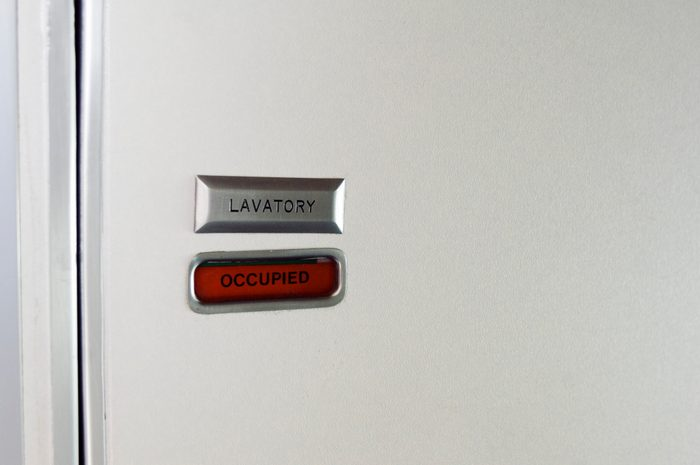 Close-up of airplane lavatory door with sign reading 'occupied'
