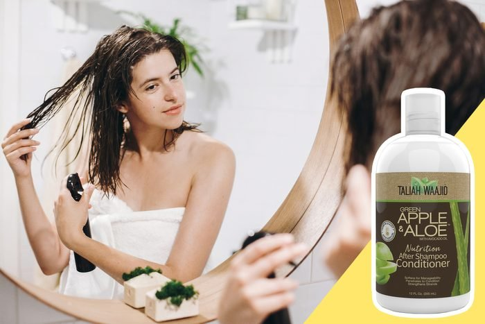 woman applying leave in conditioner spray