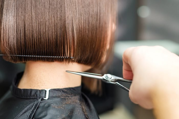 Hairdresser's hands are cutting brown short hair.