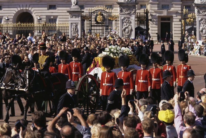 Mourners watch as the Queen's Life Guard escorts the coffin of Diana, Princess of Wales outside Buckingham Palace during her funeral
