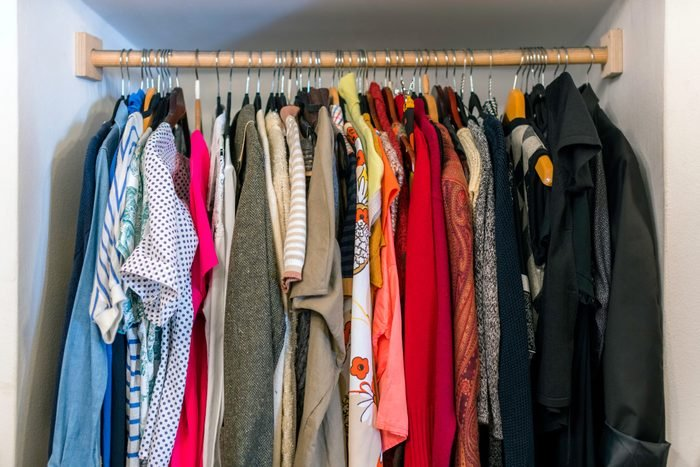 Wardrobe full of different color, material and texture clothes, accessories in the closet