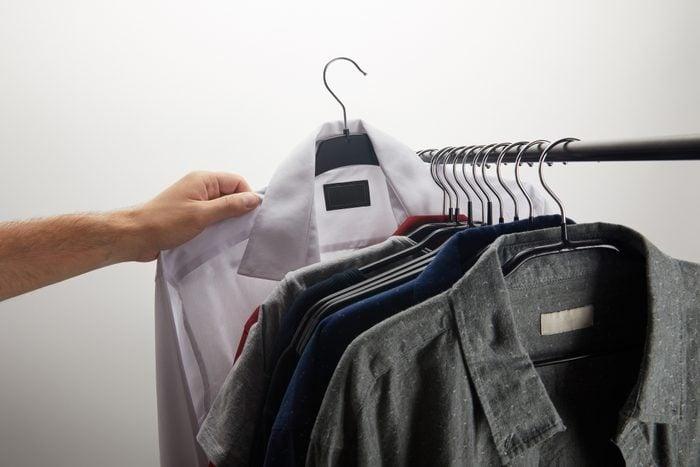 cropped image of man taking white shirt isolated on white