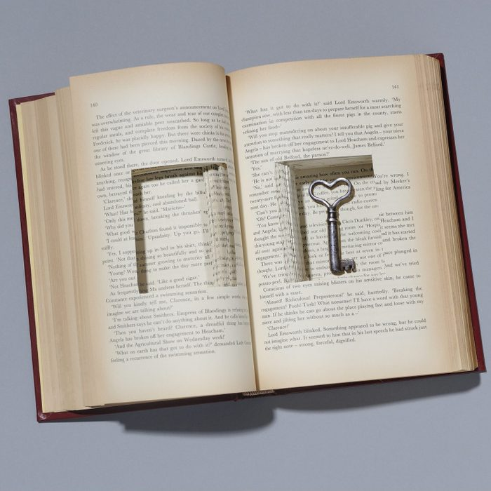 Book with key in cut out compartment.