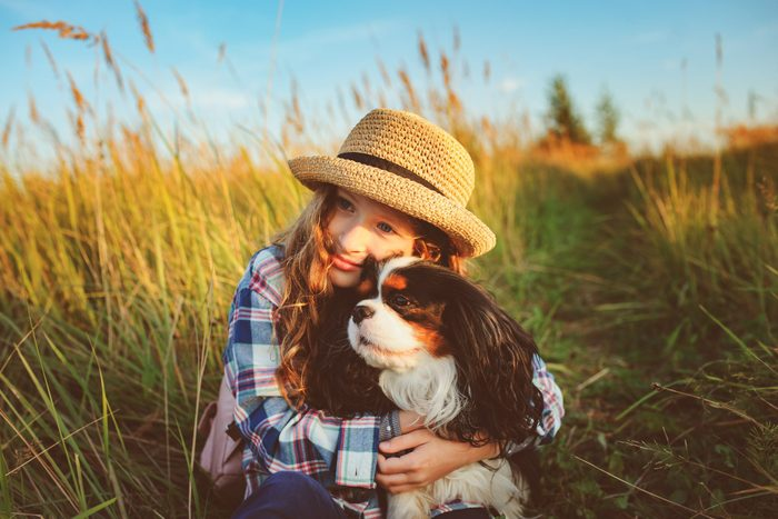 young girl hugging her cavalier king charles spaniel