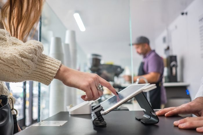 Female Customer Buying Coffee and Placing Signature On Tablet