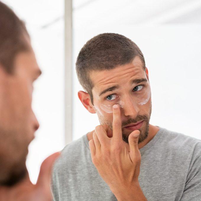 Man applying moisturizer under eyes