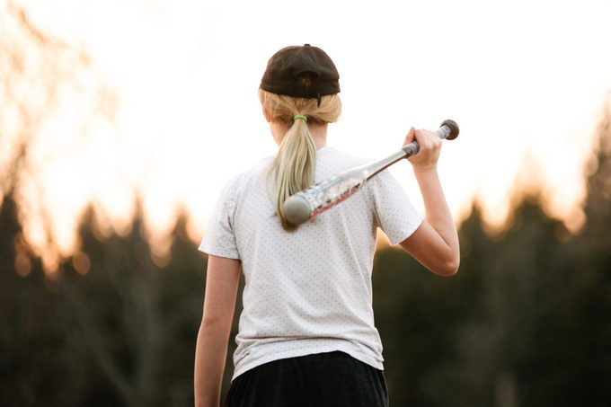 Girl with baseball bat over her shoulder in rural field, rear view