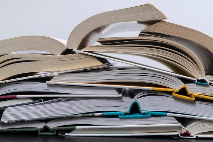 Stack Of Open Books On Table