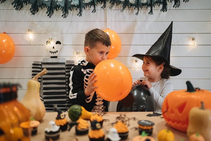 young boy blowing up orange balloon at halloween party for relay race