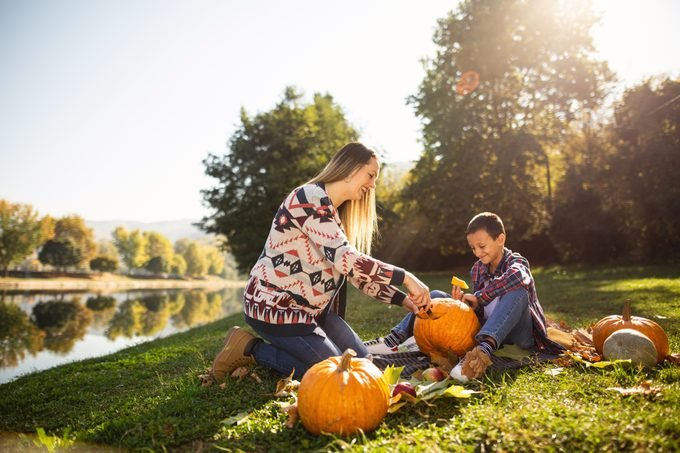 mother and son carving jack-o-lanterns in a field by a lake