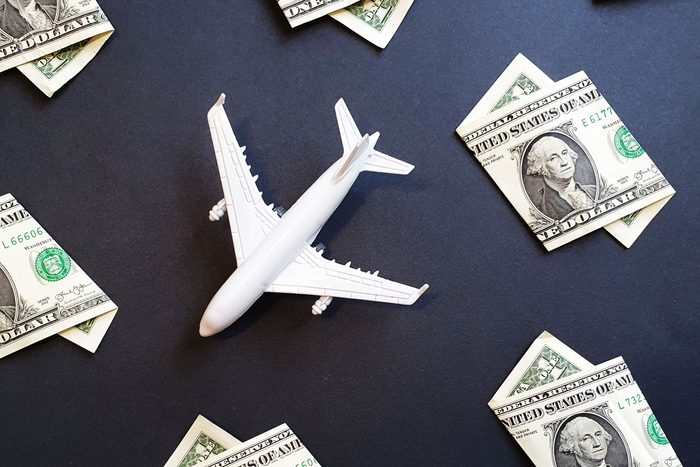 toy airplane surrounded by one dollar bills on black background