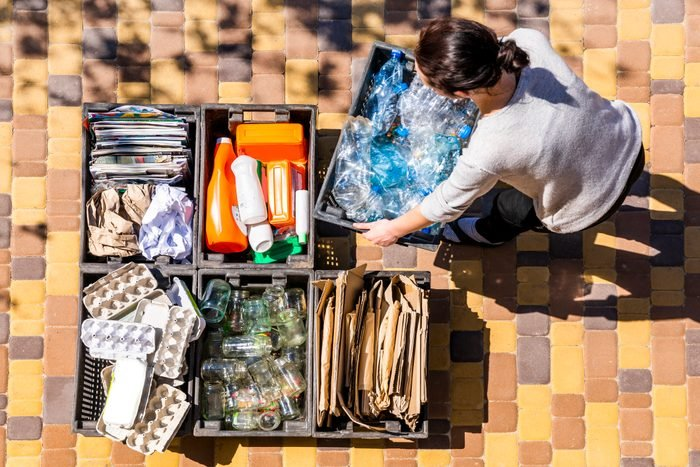 Woman organizes garbage containers for recycling.