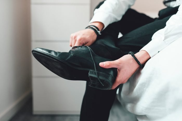 Young man putting on shoes, sitting on bed