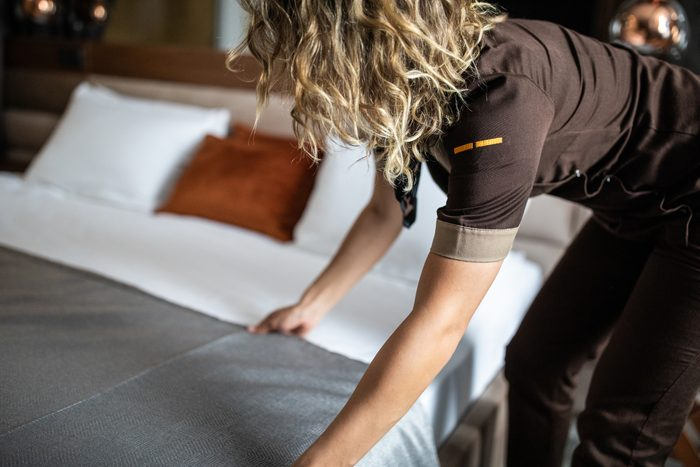 Chambermaid making bed at hotel suite