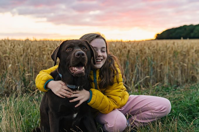 Young girl cuddling her chocolate labrador retriever at sunset
