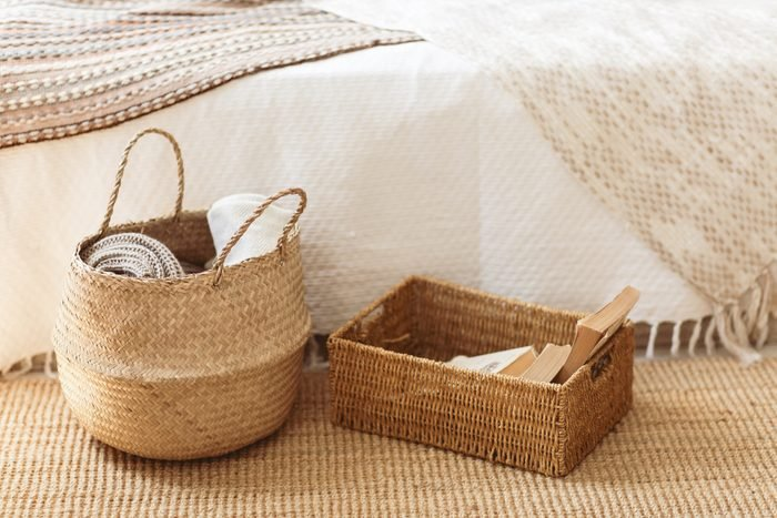 Folded gray knitted plaid in straw basket on wicker carpet near bed. Cozy hygge home style. Fall winter season concept. Close up, copy space.