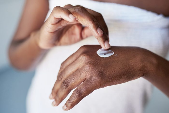 womans hands rubbing in a dab of moisturizer cream