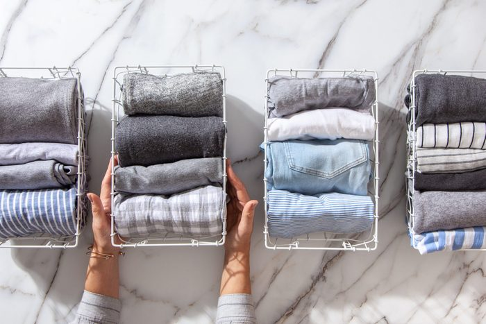 Neatly folded clothes and pyjamas in the metal mesh organizer basket on white marble table