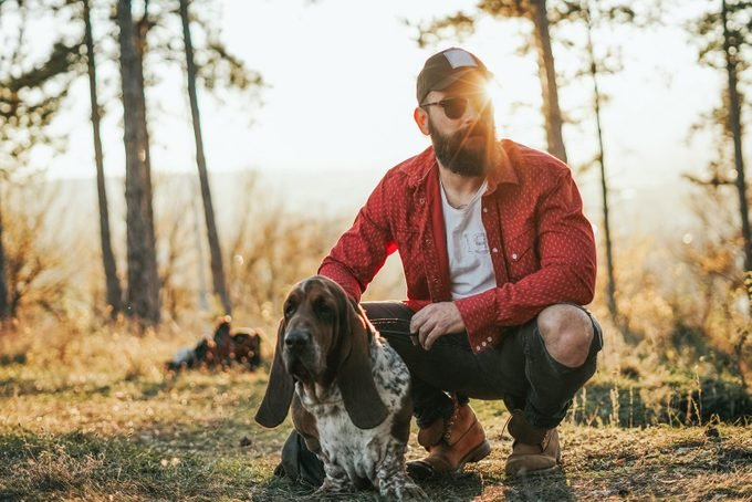 Portrait of Bearded man with a basset hound dog in nature