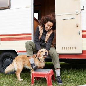 Woman sitting with golden retriever on doorway of camper van