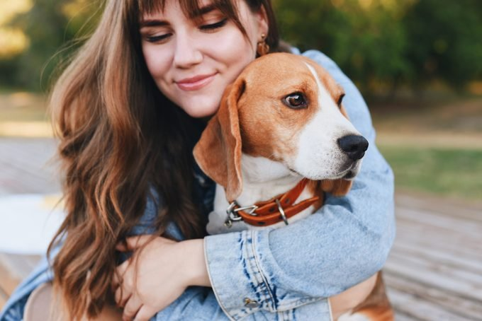 young girl hugging her beagle dog