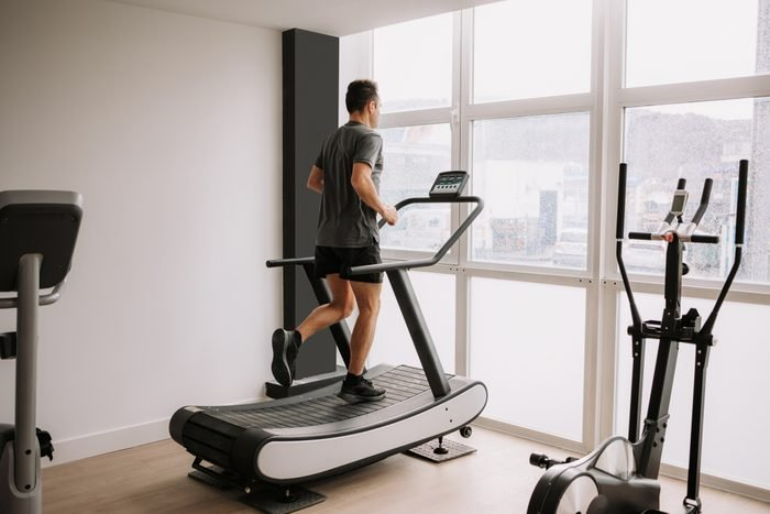 Caucasian adult man running on a treadmill in the gym next to a large window